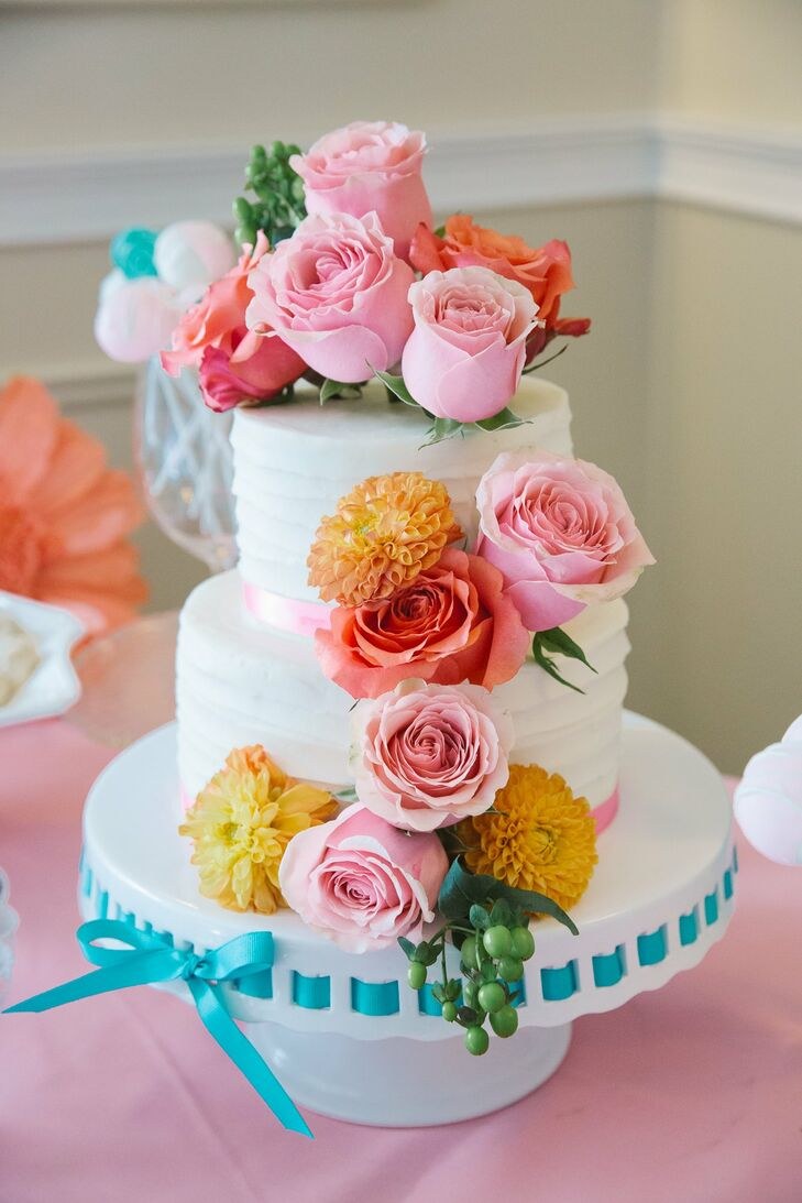 The simple two tier cake was decorated with fresh bunches of bright pink and coral roses and yellow dahlias.