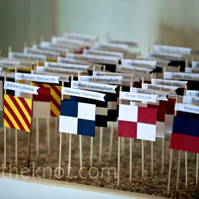 Mini nautical flags in different patterns directed guests to tables topped with matching flags.