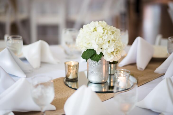 Mandy designed all the reception dining tables' decor using elegant and rustic elements. She chose white hydrangeas, surrounding candlelight and burlap table runners.
