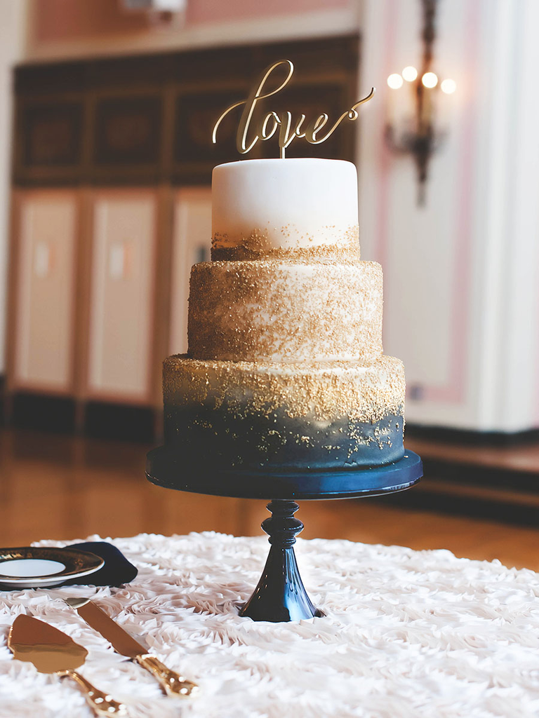 Navy and gold wedding cake with calligraphed cake topper
