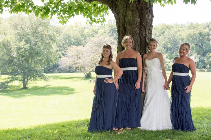 The bridesmaids wore floor length, navy dresses with ruffles by Vera Wang for David's Bridal. They paired their dresses with ivory sashes.