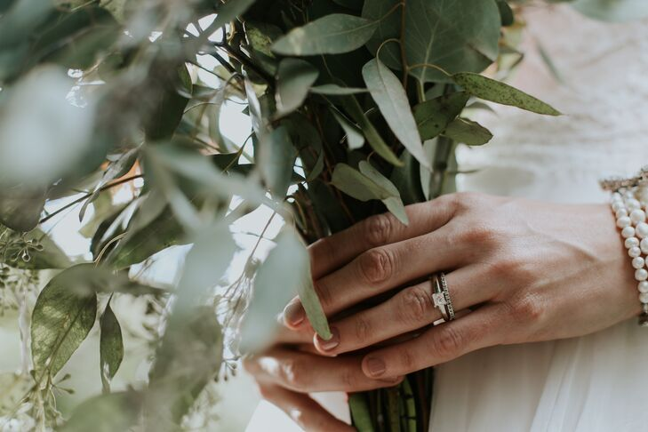 Inherited from Jeremy's grandparents, Christian wears a princess-cut diamond set on a simple band accompanied by a pave diamond wedding band.