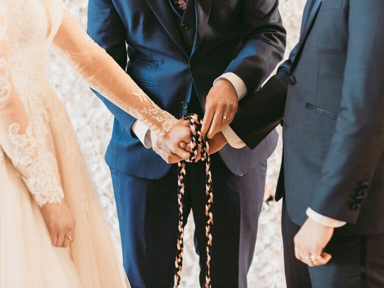 Bride and groom having hands tied with rope during traditional handfasting ceremony