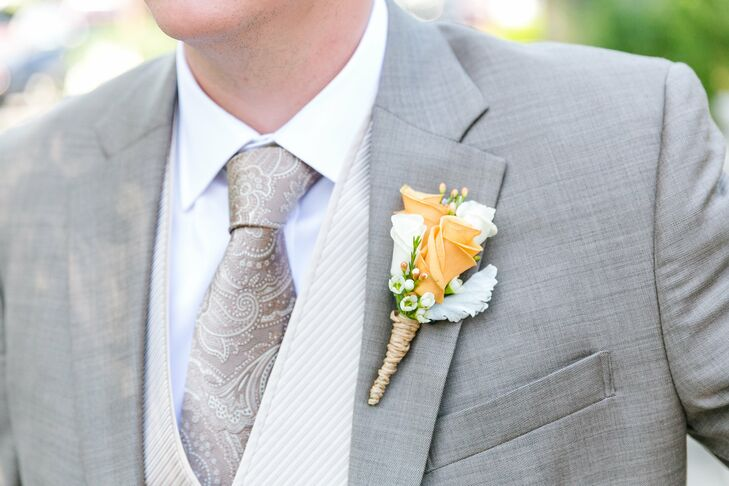 A cluster of rose buds accented with wax flower and dusty miller made up the groom's boutonniere.