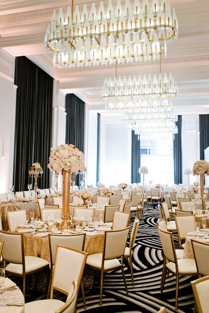 The ballroom at Kimpton Hotel Monaco Pittsburgh in Pittsburgh, Pennsylvania, was outfitted with a number of round tables covered in gold tablecloths. Tables featured alternating high and low centerpieces of blush and ivory blooms.