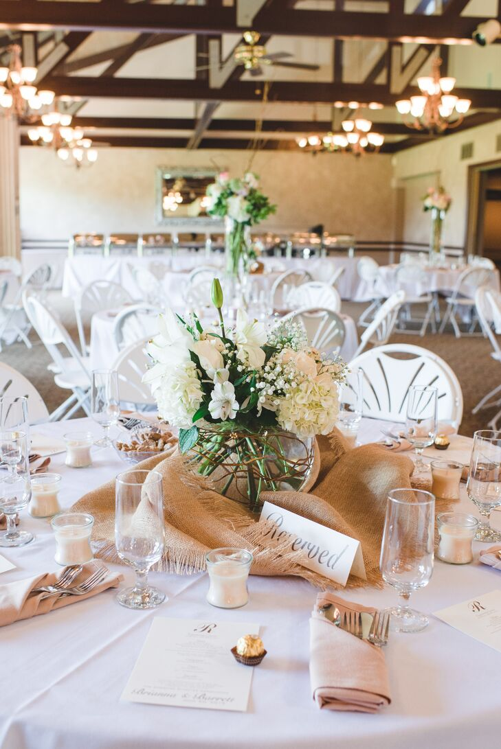 For the low centerpieces, an all-white assortment of florals, like hydrangeas, orchids, lilies and more, filled round vases laced with curly willow and were displayed a top burlap linen for a rustic-meets-romantic feel.