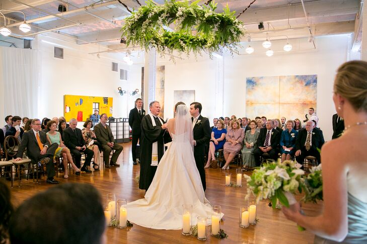 The ceremony took place inside Terra Gallery in San Francisco, California, where Chelsea and Chris stood on the hardwood floors surrounded by romantic white candles. A chandelier made up of leafy greens and ivory blooms hung from above.