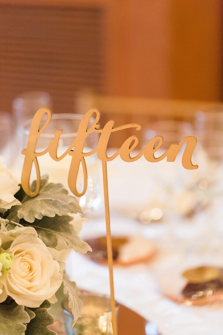 The table numbers were just as elegant as the rest of their decor. Carved into a 3-D shape, each gold table marker popped from the couple's white roses and dusty miller centerpieces. The script designs even resembled their regal font from the day's invitation suite.