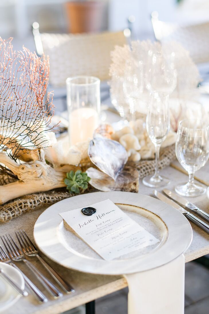 """While the centerpieces fully embodied the beach-chic theme, the place settings themselves took on a more understated tone. Antiqued white dinnerware and linens gave way to hand-lettered menu cards bearing the names of each guest and a wax """"T"""" seal."""