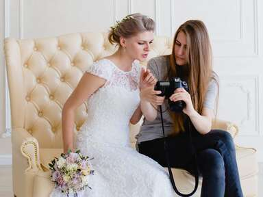 Bride and photographer looking at camera roll