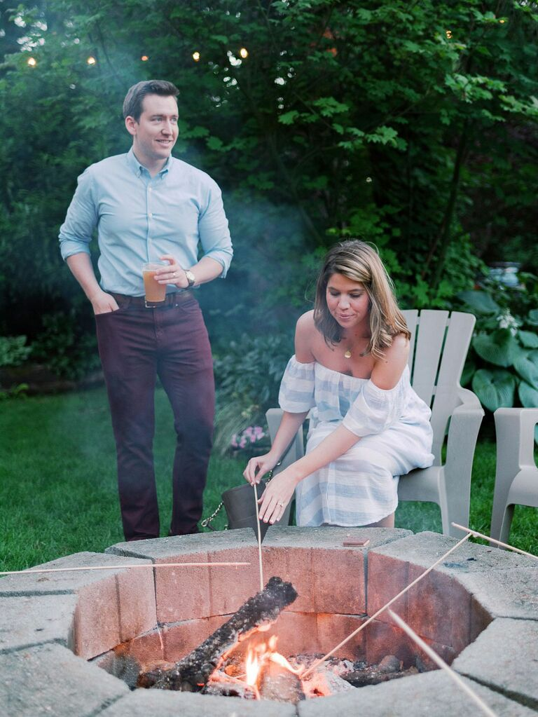 Bride and groom roasting S'mores at casual outdoor backyard summer wedding