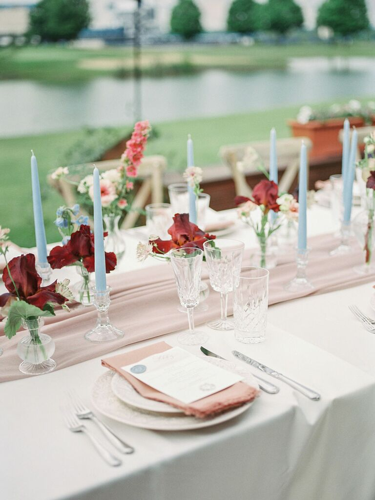 Simple wedding reception center pieces with minimalist red flowers and blue candlesticks