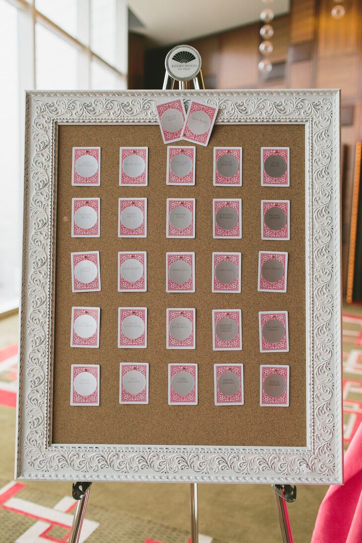 Inspired by Las Vegas, Nevada, Kaitlyn created the escort cards herself and displayed them on a white-framed board. Circular silver stickers with guests' names were attached to the back of playing cards, each with a number that determined where they sat for the reception.