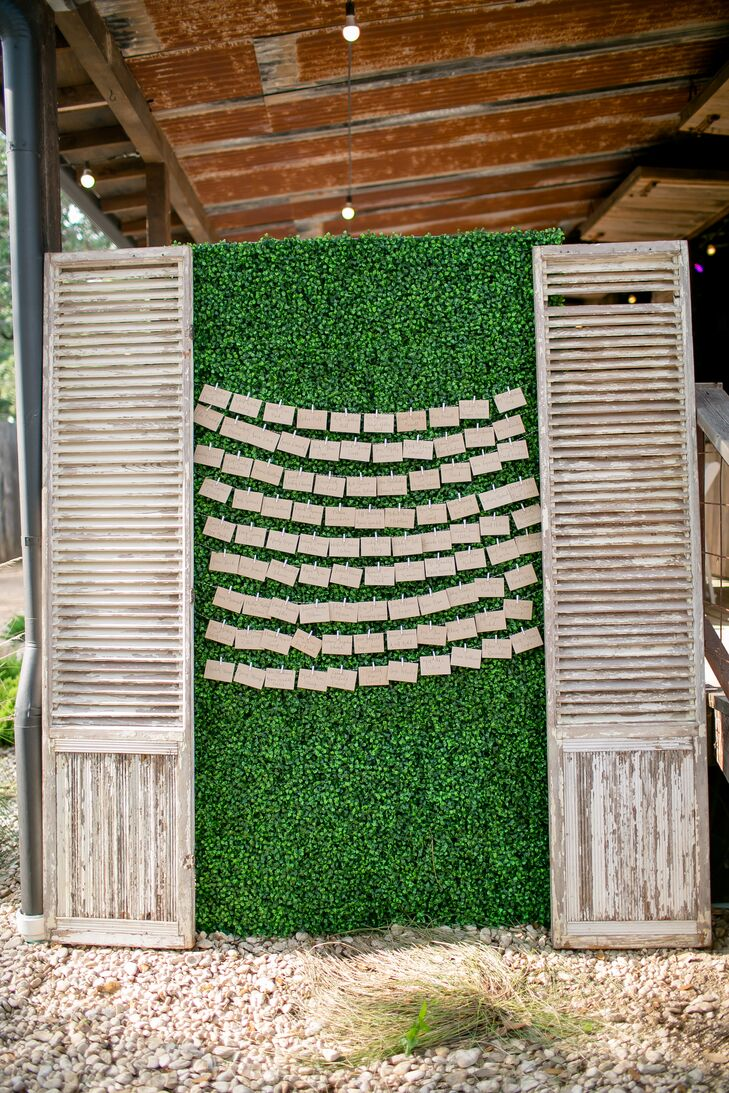 Escort cards were displayed on lush greenery and flanked by rustic shutters.
