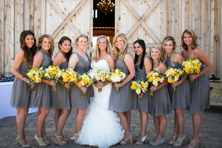 Lauren stood in the middle of her bridesmaids dressed in charcoal gray knee-length dresses, with the on-site barn as a backdrop. Although the women wore the same-colored dress, each had a completely different style.