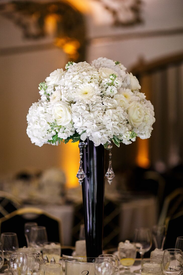 Westmont, Illinois, florist Bella Flora worked closely with the couple to create large, black-and-white flower arrangements using an assortment of hydrangeas and roses. To add to the elegant feel of each arrangement, clear crystals were draped across each centerpiece.