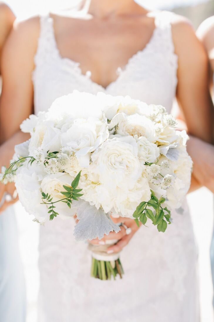 """My bridal bouquet was a breathtaking, hand-tied loose romantic round style, consisting of patience ivory roses, gardenias, garden roses, lisianthus, dusty miller and sprigs of greenery,"" Leah says. ""I wanted a lot of white in various shades and textures and used the dusty miller to add a touch of light blue and velvet texture. I used a handkerchief from my grandmother to tie the flowers together."""