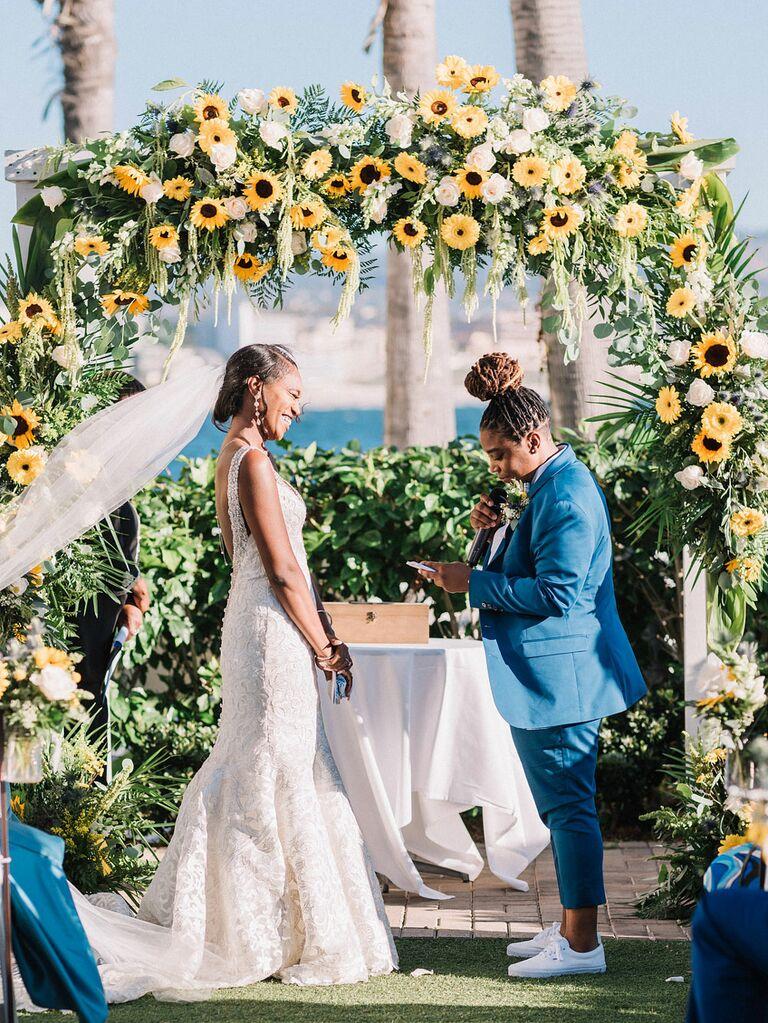 Brides saying vows at outdoor wedding under sunflower arch
