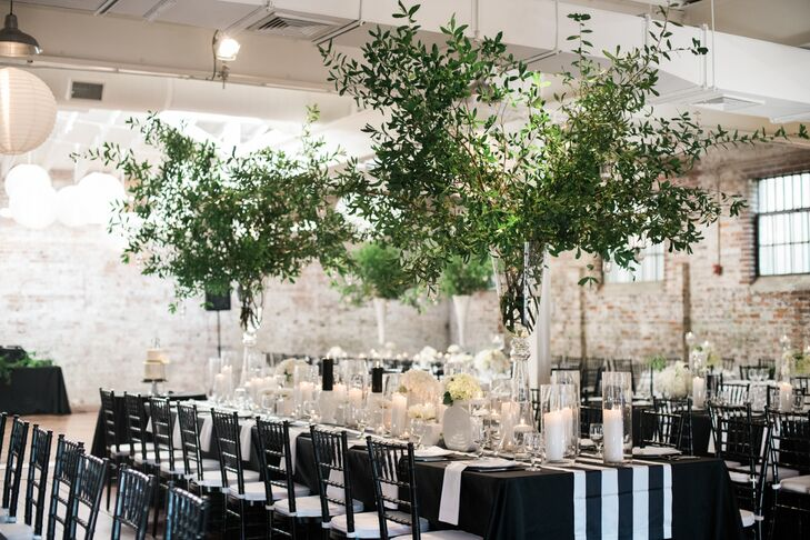 "Tree branches were used in lieu of floral arrangement centerpieces at the reception at Bakery 105 in Wilmington, North Carolina. ""The venue space is industrial and raw, so the tree branches added the right amount of texture and movement to give life to the space,"" Joy says. They were also more reasonably priced than blooming flowers."