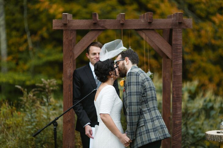 The bride's brother built the wooden ceremony arbor by cutting the slabs from a fallen tree. Katie and Jeff hung geometric glass terrariums of light and dark green moss from the top of the arbor and stood in front of it during the ceremony.