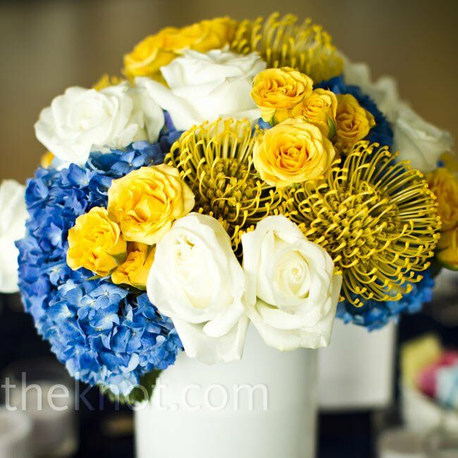 Blue hydrangeas, yellow proteas, and white and yellow roses, set inside white vases wrapped with preppy striped ribbon, decorated the tables.