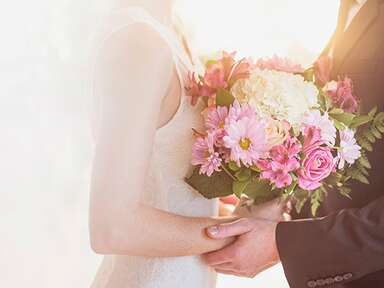 Bride holding a pink and white bridal bouquet, held in her father's hands