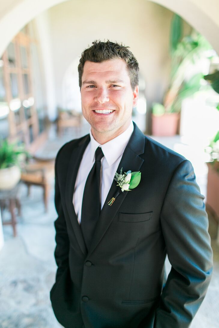 Greg and his groomsmen wore traditional black suits with crisp white shirts and delicate white rosette boutonnieres.
