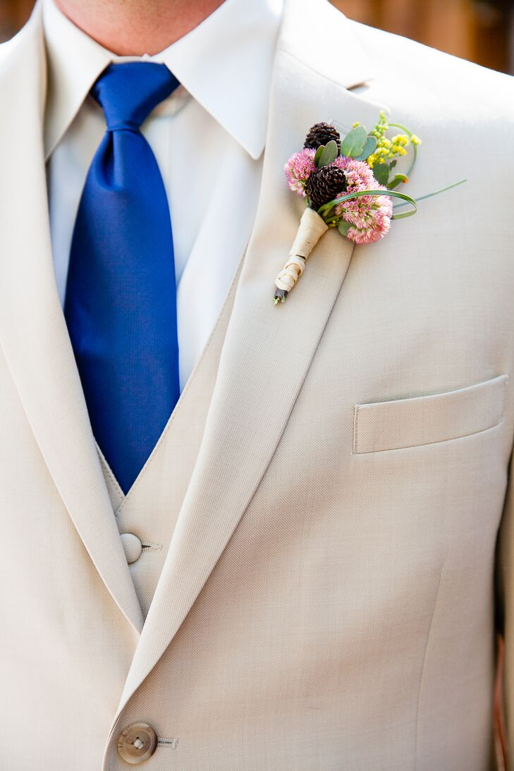 Gregory wore a light tan three-piece suit with a boutonniere pinned to the lapel, made with a mix of pinecones, sedum and small accents of greens. Gregory wore a royal blue tie over a white collared dress shirt.