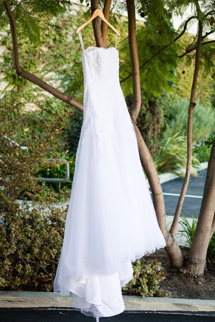 """""""Micaela's wedding dress was strapless with a fitted bodice and flared skirt. The bridesmaids wore long coral colored gowns with two straps,"""" says the couple. """"The majority of the groomsmen wore service dress blue uniforms, and the groom's older brother wore a gray suit."""""""