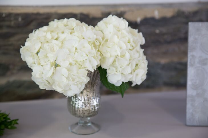Bunches of white hydrangeas were displayed in mercury glass vases for the centerpieces.