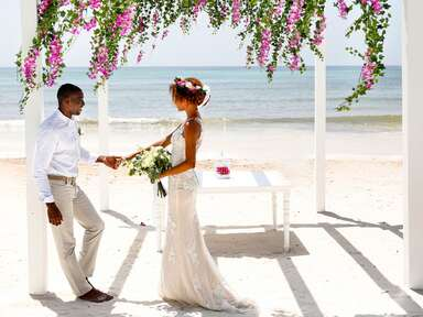 wedding ceremony on the beach with hanging flowers