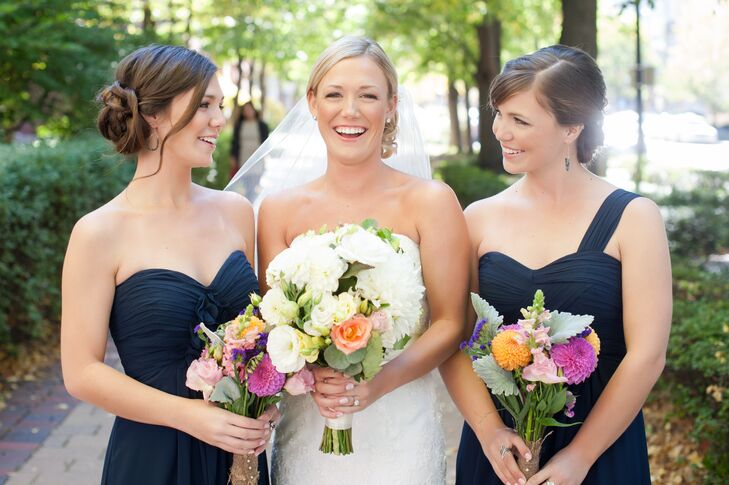The bridesmaids wore similar floor-length navy blue dresses with differing straps, including strapless, one-shoulder, and V-neck styles. Their colorful bouquets popped against the dark, monochrome dresses.