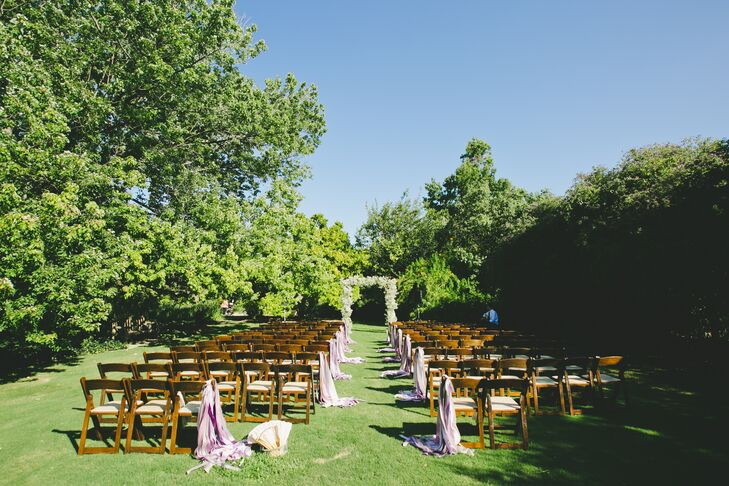 Esme and Matthew's 135 guests sat on wooden chairs for the outdoor ceremony; bouquets of lavender ribbons decorated the aisle, reflecting the event's palette of lilac, cream and gray.