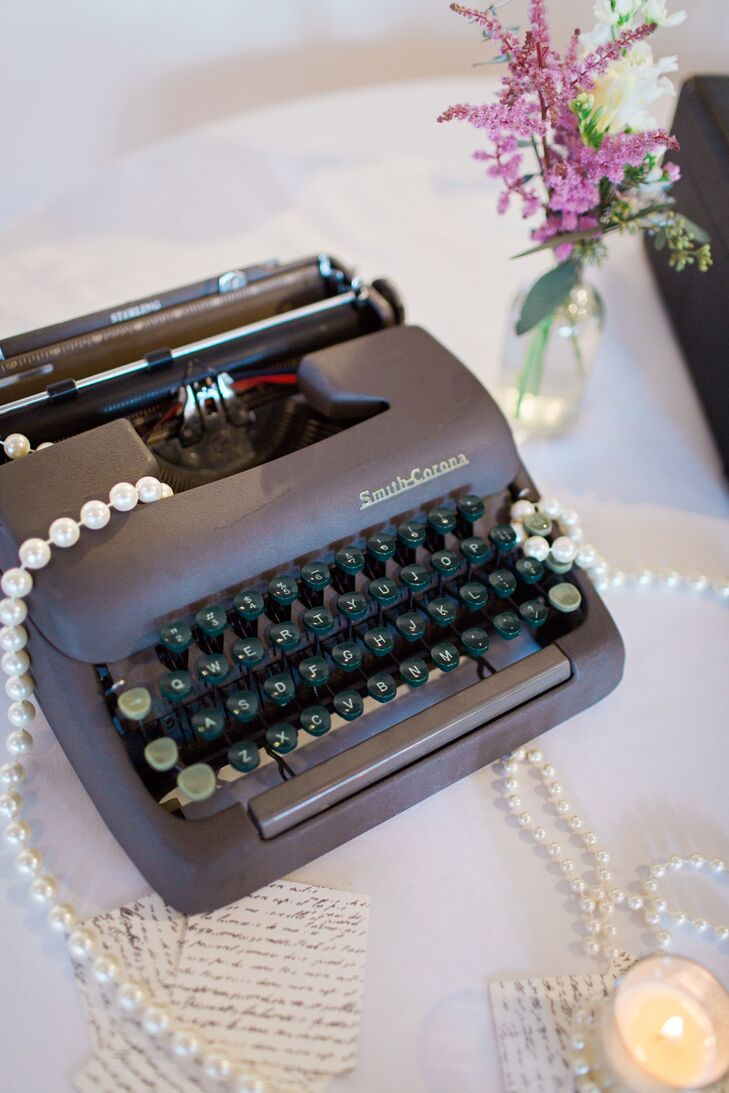 Inspired by a photo they found online, Alex and Bobby decorated their reception with a vintage typewriter, suitcases, stacked books and low mismatched floral centerpieces.