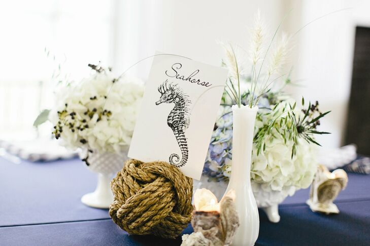 Knotted rope held the table cards, which were nautical in design. Flowers in vintage milk glass vases completed the look.