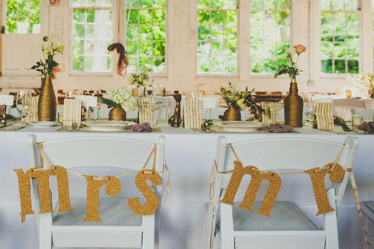 """The long dining table where the bride and groom sat at the reception was marked by the back of the chairs with """"Mr."""" and """"Mrs."""" gold signs. High and low vases wrapped in twine with arrangements of roses, hydrangeas and veronica decorated the surface of the tables."""