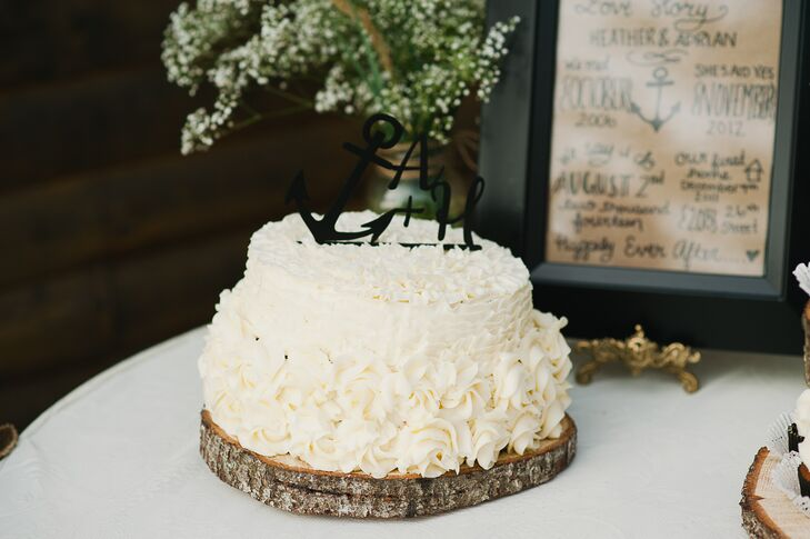 The small white cake was covered in a frosted rose design. A black anchor and the couple's initials stood on top as the cake topper.