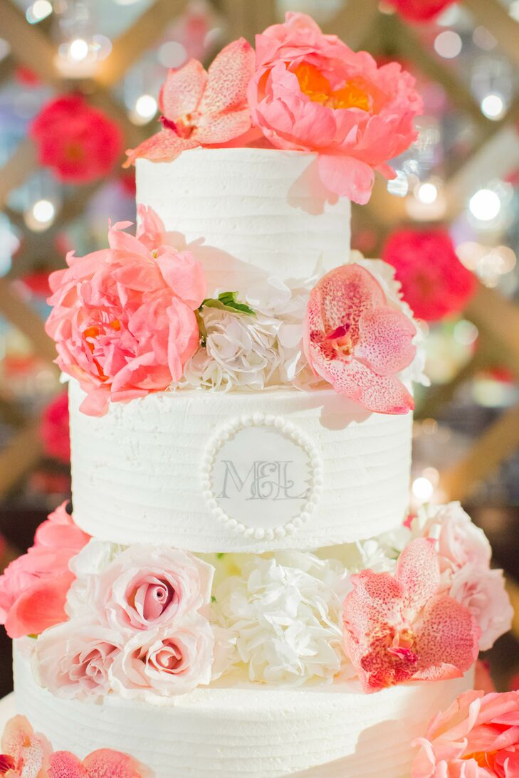 The ivory cake was white chocolate with raspberry cream filling and chocolate cake with espresso cream filling, decorated in pink peonies and the couple's personalized monogram.