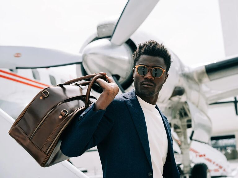 Man holding brown leather weekender over his shoulder about to board flight