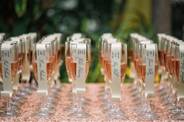 """The escort cards were a shaped like tiny scrolls and hung from glasses of pink champagne. """"I loved these,"""" Lona says. """"I searched long and hard for a unique and fun escort display that wouldn't break the bank."""""""