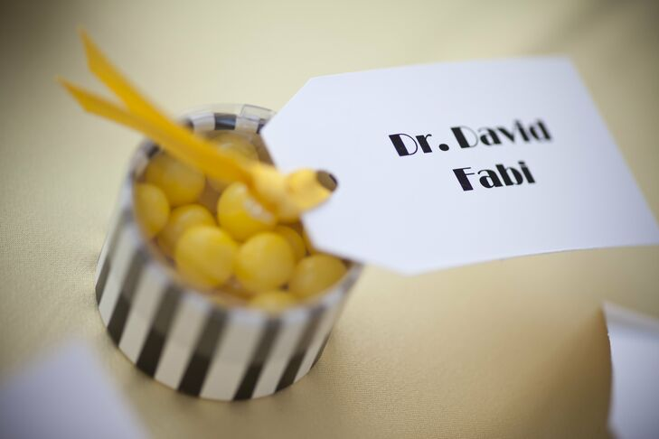 The gift tag escort cards were tied with yellow ribbon to modern black-and-white striped boxes filled with yellow candies.