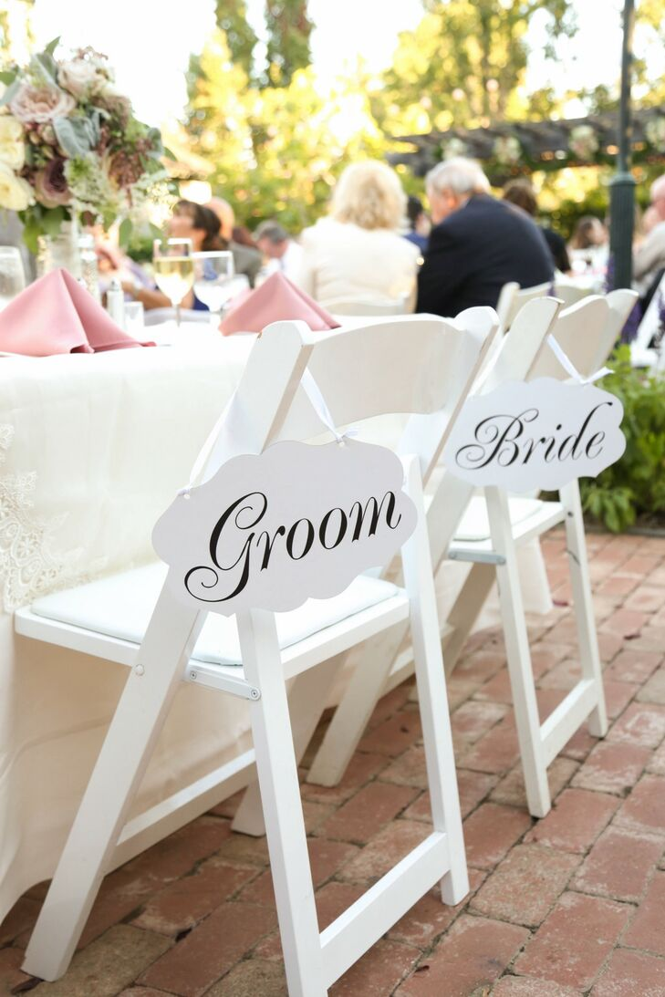 """""""Groom"""" and """"Bride"""" white signs hung from folding chairs at the sweetheart table."""