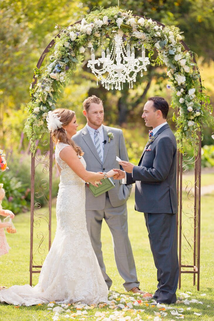Sophie and Ryan were married outside on the Rancho Soquel property, where they stood at the iron wedding arch decorated in a lush garland of greenery and flowers. A single white chandelier hung from the arch as Sophie and Ryan read their vows to one another.