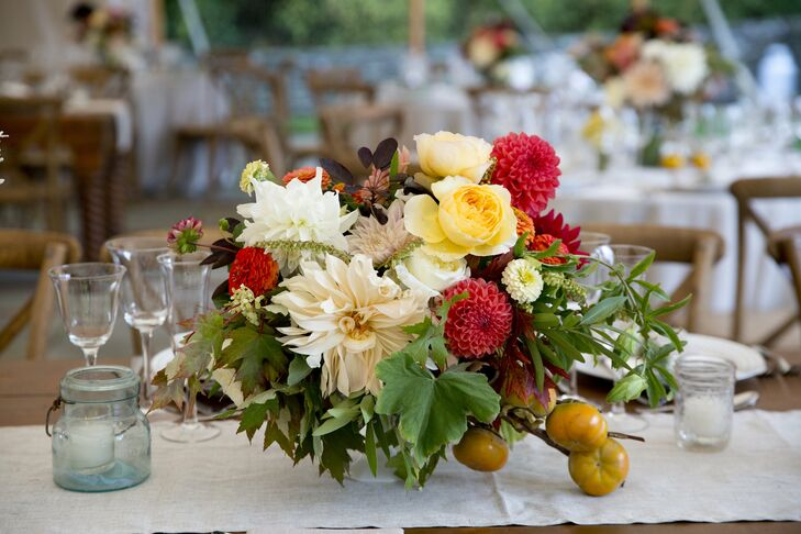 Low centerpieces of poppy pods, garden roses, Queen Anne's lace, snapdragons, dahlias and hydrangea along with grasses, herbs and fruits sat atop long wooden tables with linen runners.