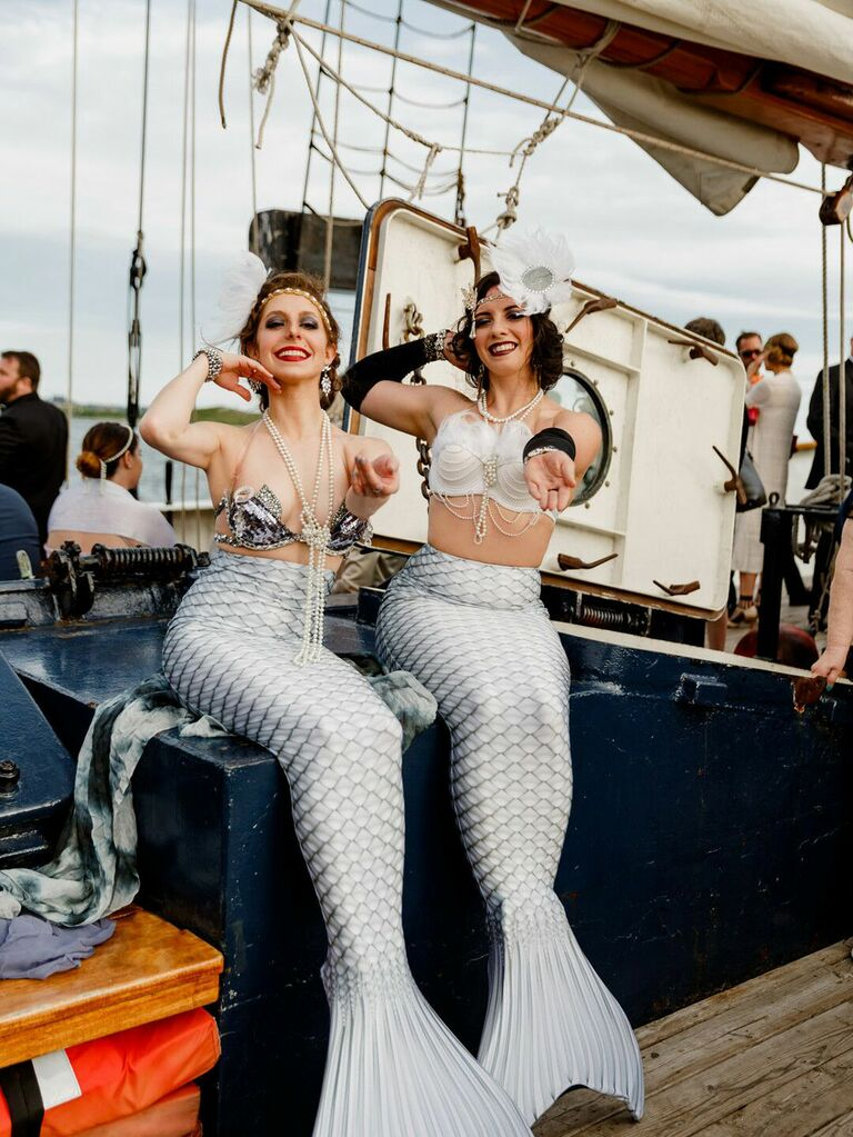 Entertainers dressed as mermaids at nautical summer wedding on boat