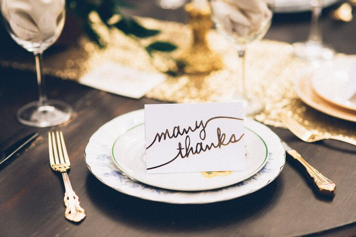 An ivory thank you card with metallic gold lettering awaited each guest at their place setting with a photo of the couple tucked inside.