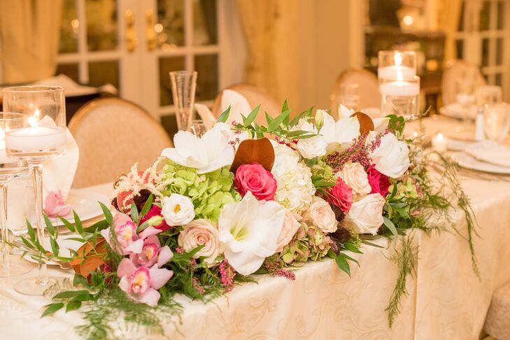 Reception centerpieces alternated between high and low arrangements with the latter featuring a long display of ivory, blush and pink florals and greenery paired with floating votive candles in clear glass vases.