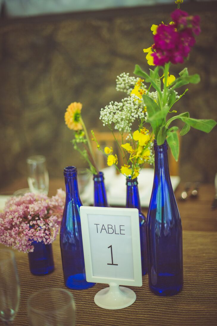 Table numbers and centerpieces were kept simple with royal blue glass wine bottles filled with single stems of colorful flowers to match the bride's bouquet. At every place setting, cookies from the Honolulu Cookie Company served as favors, along with notes indicating a donation was made to the Wounded Warrior Foundation and the National Multiple Sclerosis Society.
