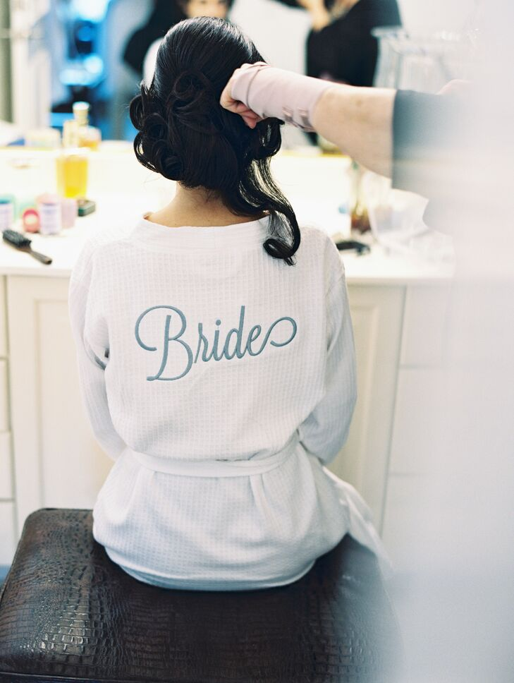 "While preparing for her wedding day, Monique donned a simple white robe with ""Bride"" embroidered in blue on the back."