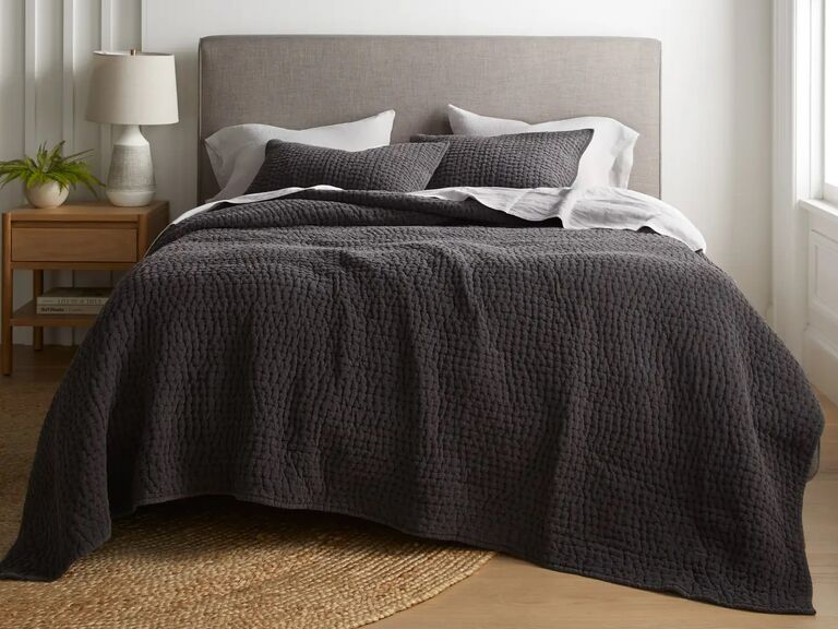 Charcoal gray cotton quilt and pillows shown on a bed